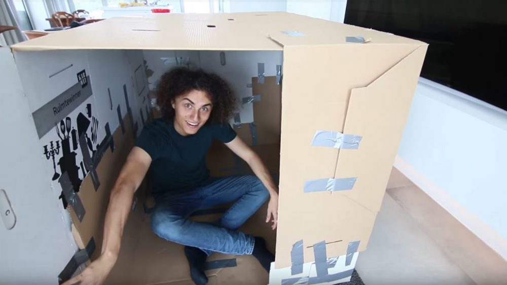 guy sitting in small box fort
