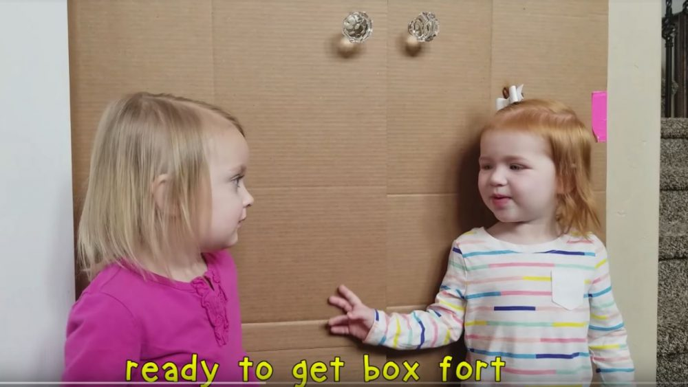 two little girls in front of box fort doors