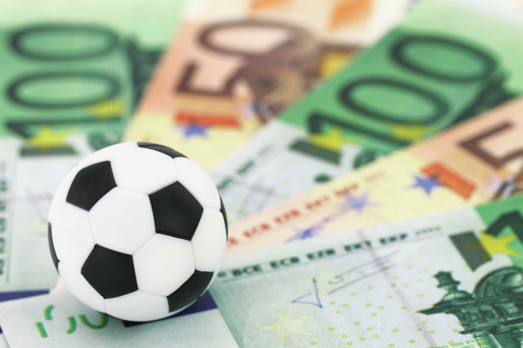 Close-up of a toy soccer ball atop European money bills