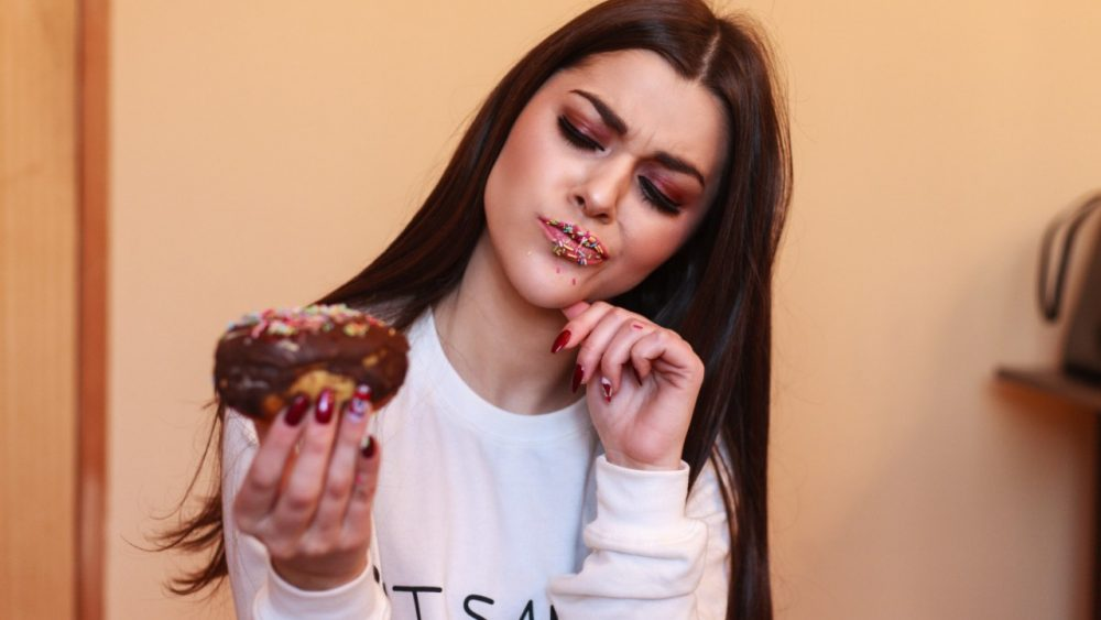 girl eating donut and looking at it critically