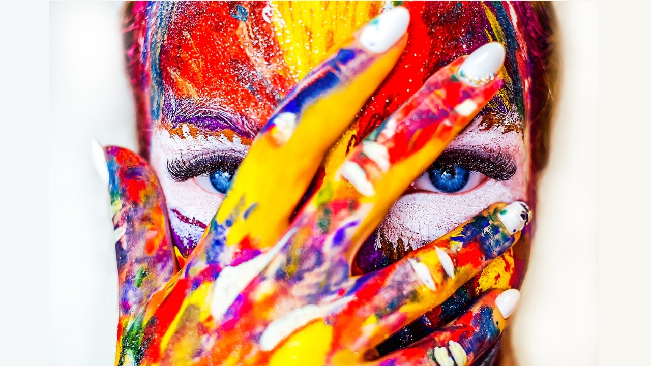 colorful paint on face with hand over face
