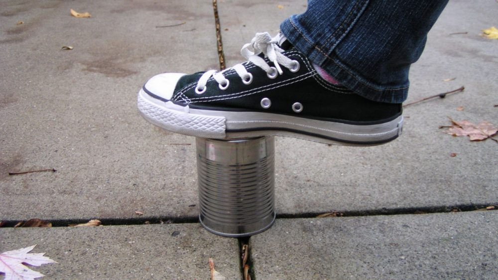 person stepping on tin can kick the can game