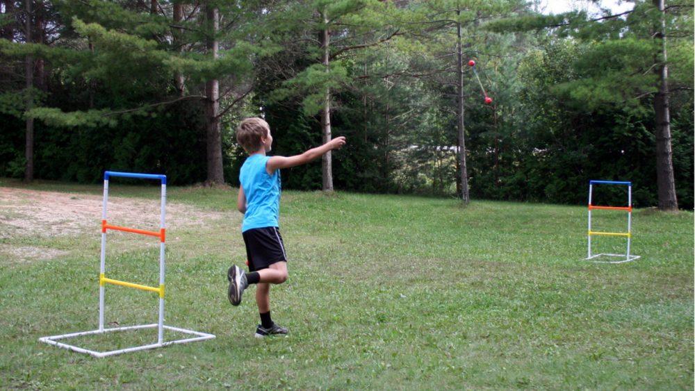 boy playing ladderball in yard