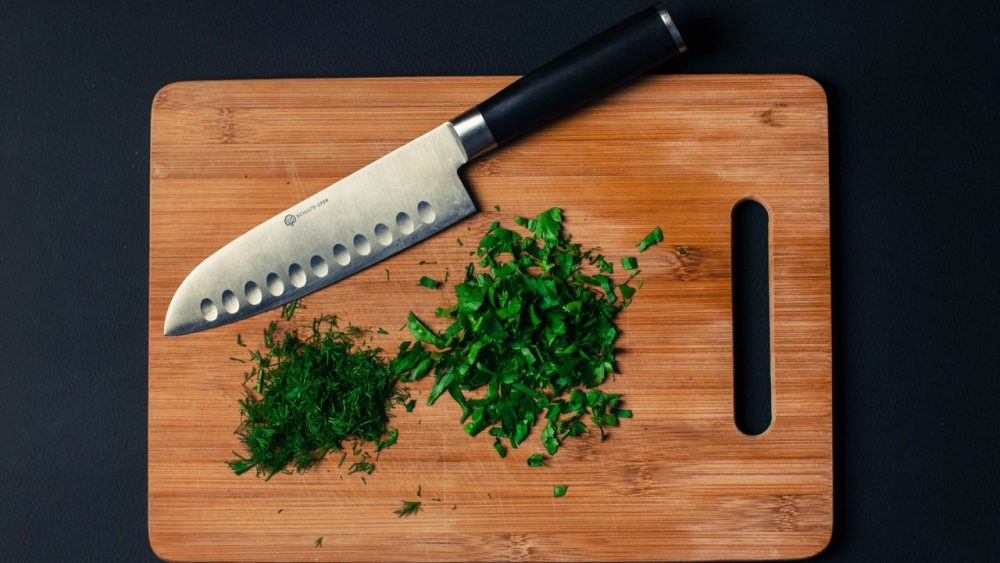 knife on cutting board with chopped herbs