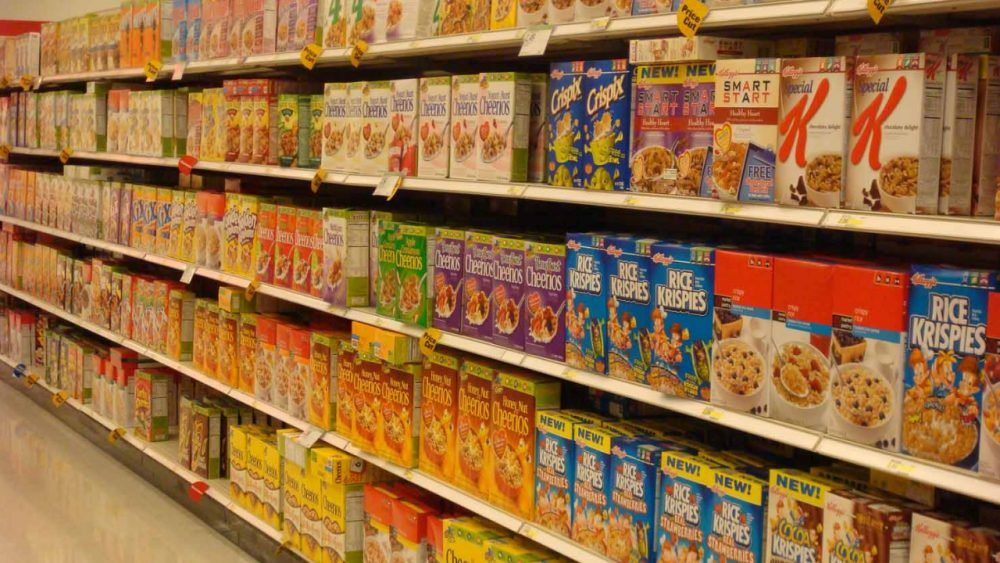 variety of name brand cereals on grocery store shelf