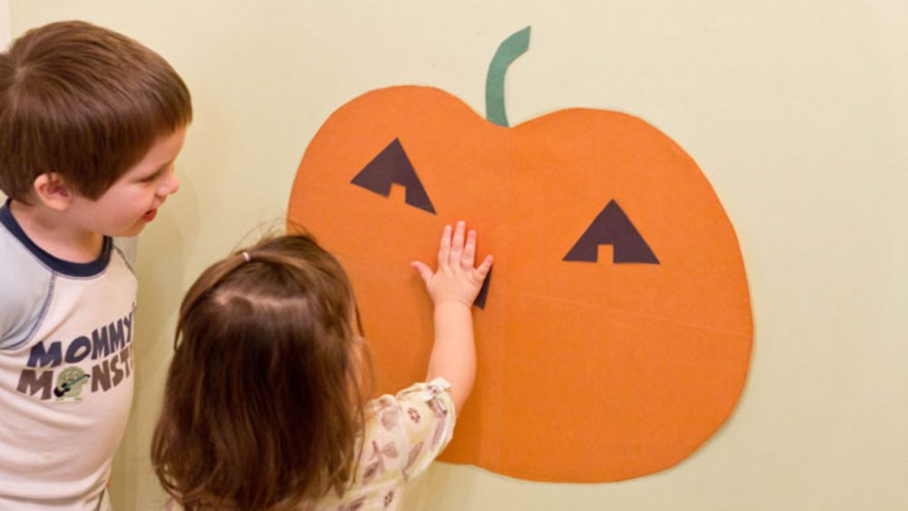 kids playing pin the face on the pumpkin