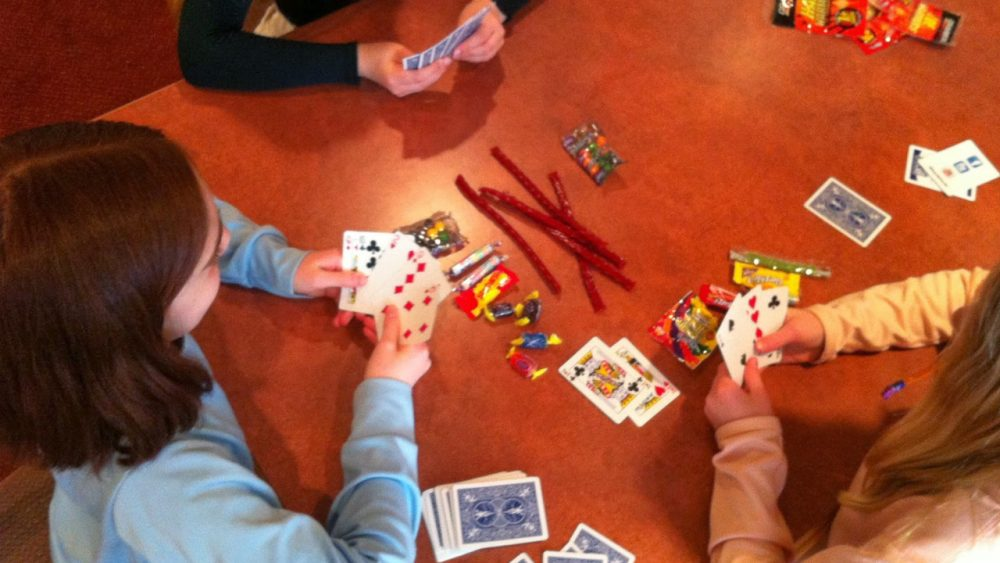 family playing card game with candy