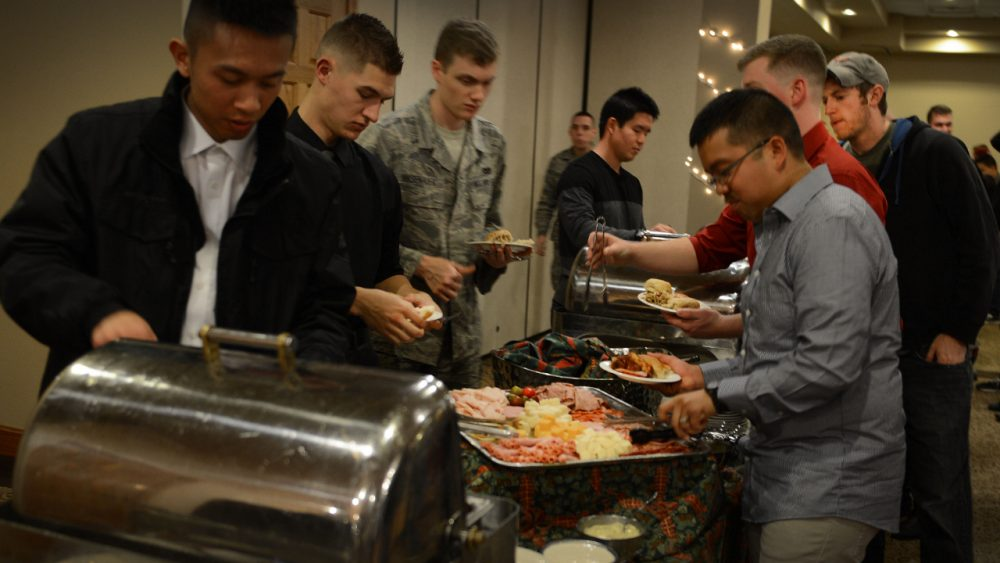 group of men getting food from buffet lineup