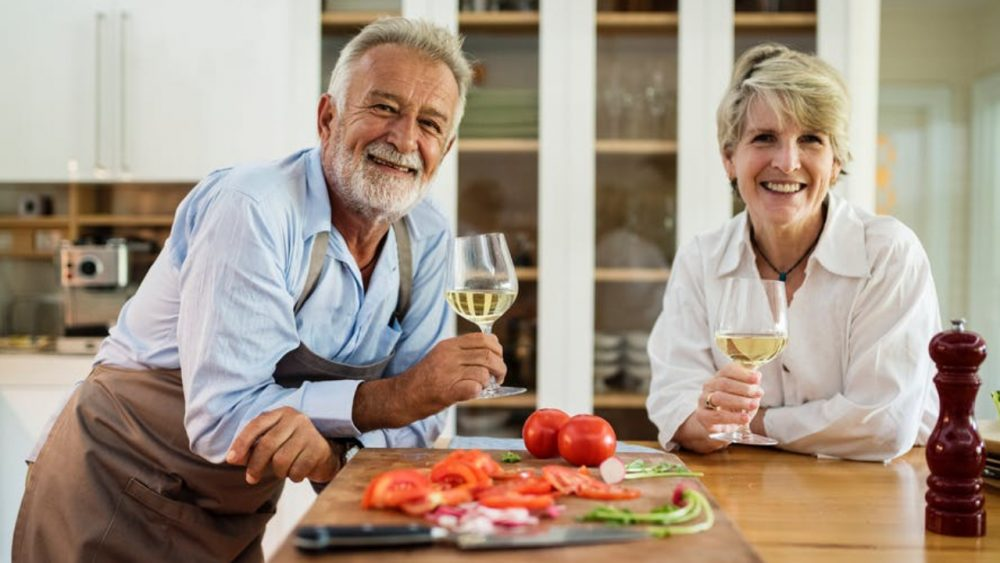 couple drinking wine and smiling in kitchen