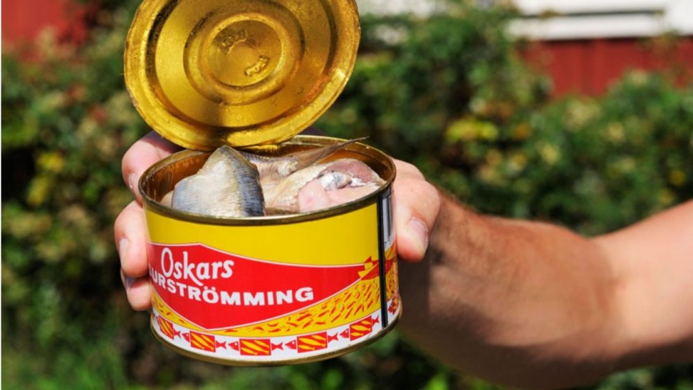 person holding open can of surstromming
