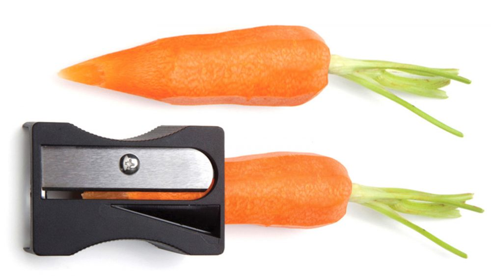 one sharpened and peeled carrot next to carrot in sharpener