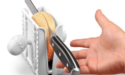 bagel in open sesame bagel slicer being cut with knife