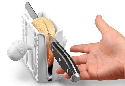 bagel in open sesame bagel slicer being cut with knife