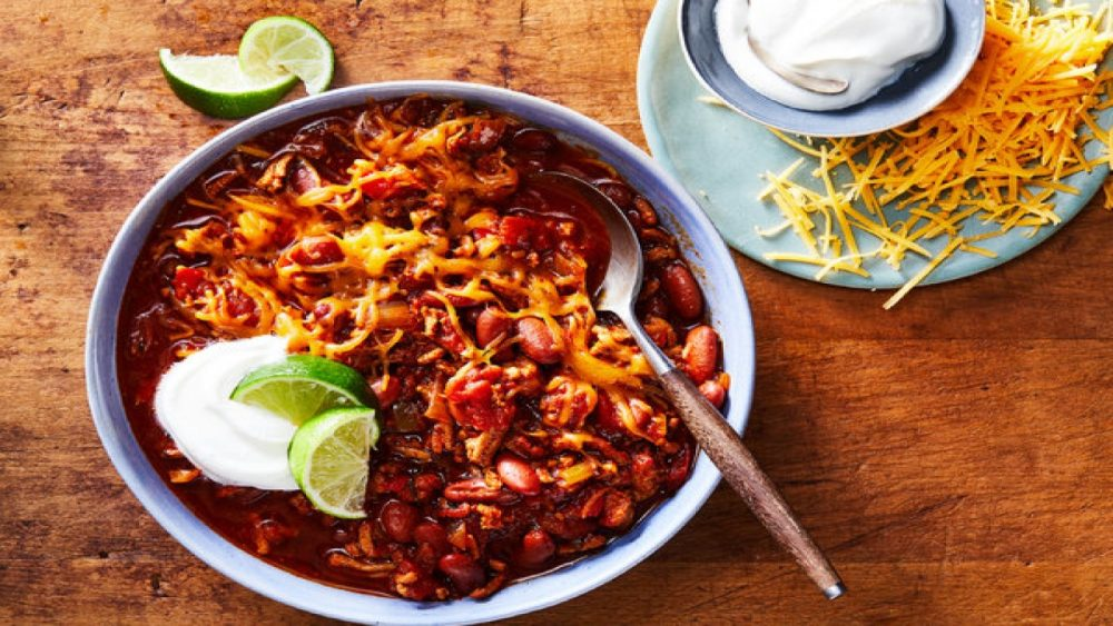 bowl of chili with cheese and toppings