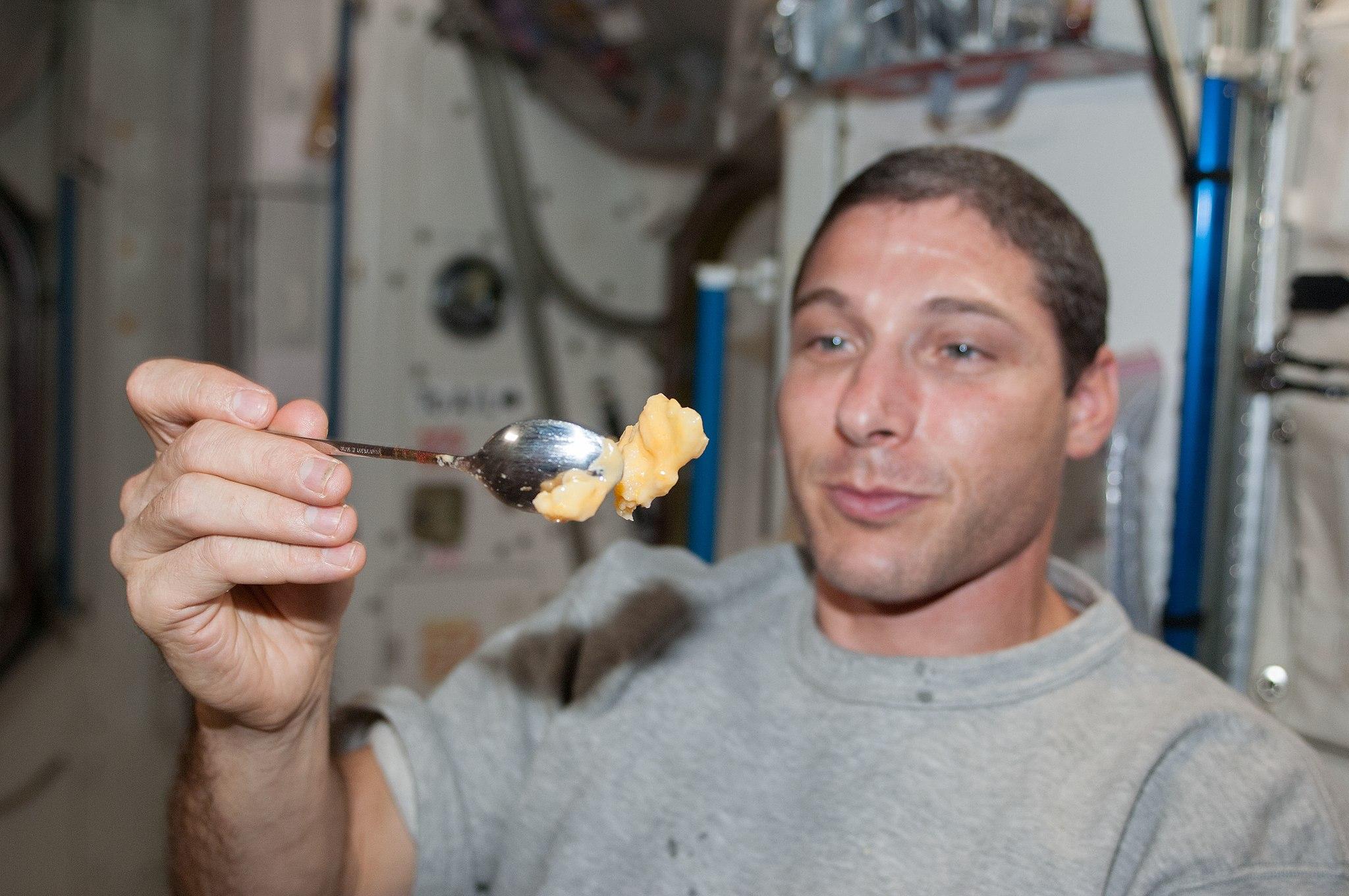 astronaut holds peanut butter spoon