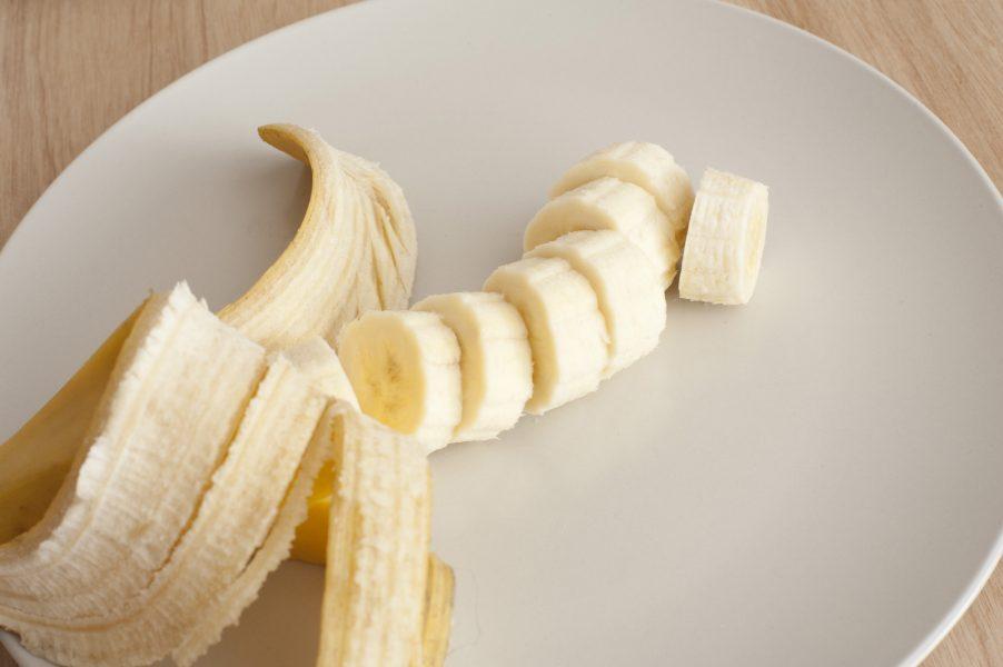 A banana peeled and sliced on light background