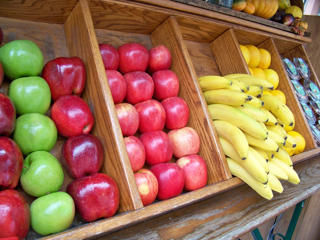 apples, bananas and other fruit in wooden baskets