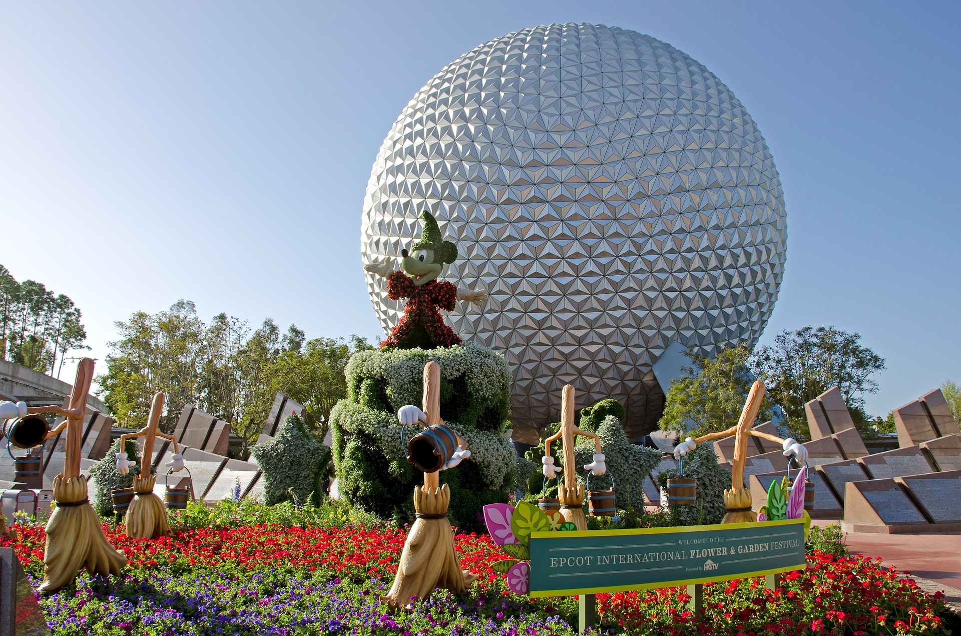 Epcot geodesic sphere behind mickey mouse in garden