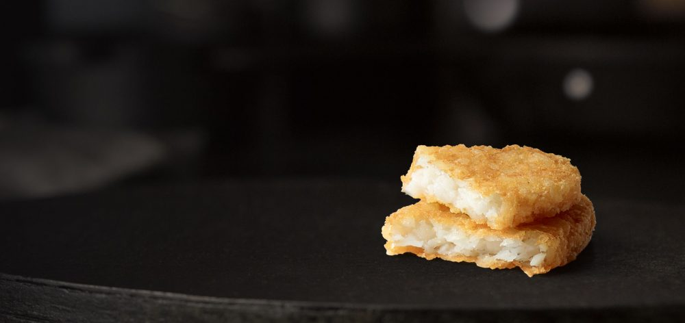 Hash brown cut in half on black background