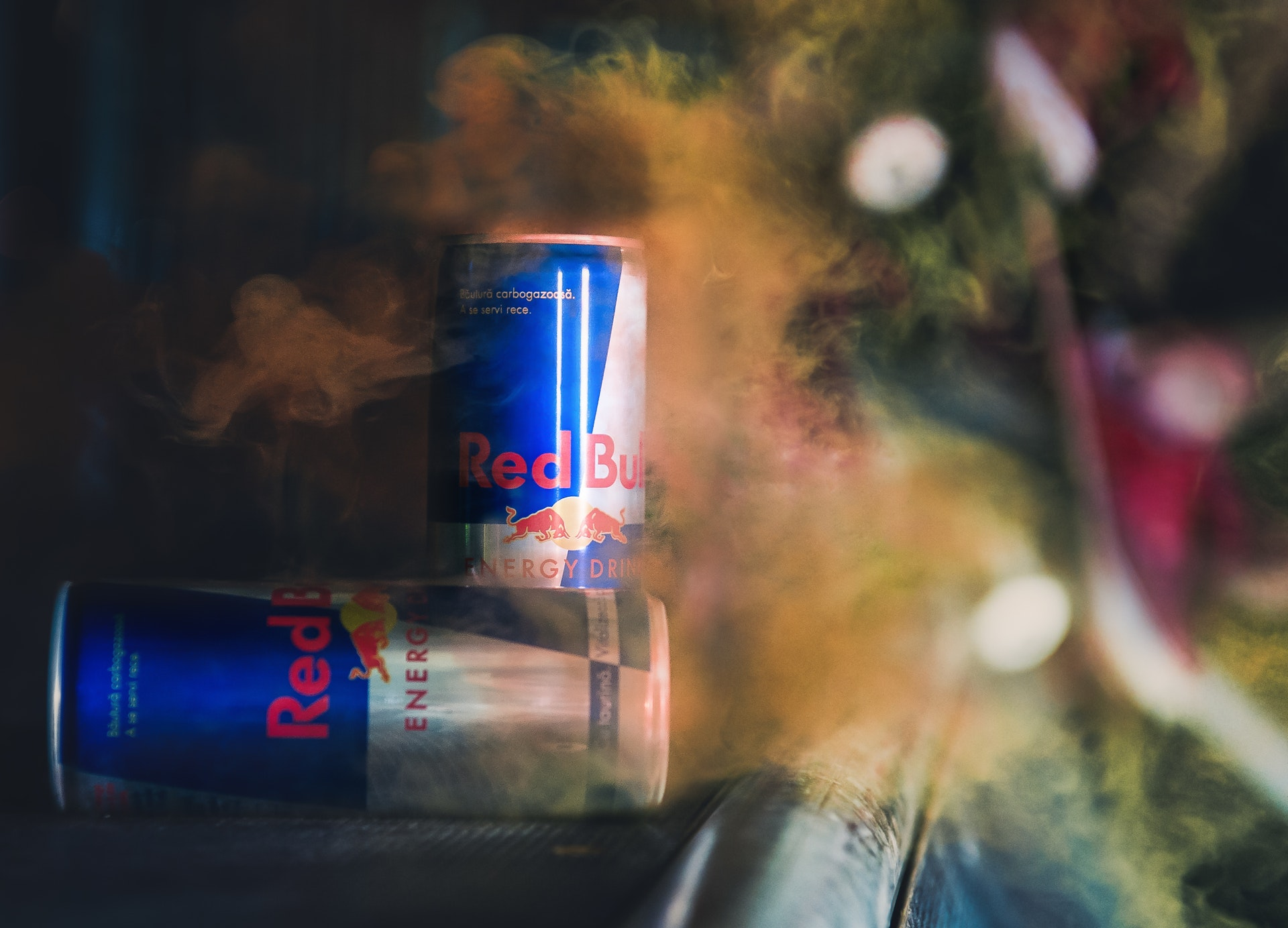 Red Bull cans in brown vapor or dust