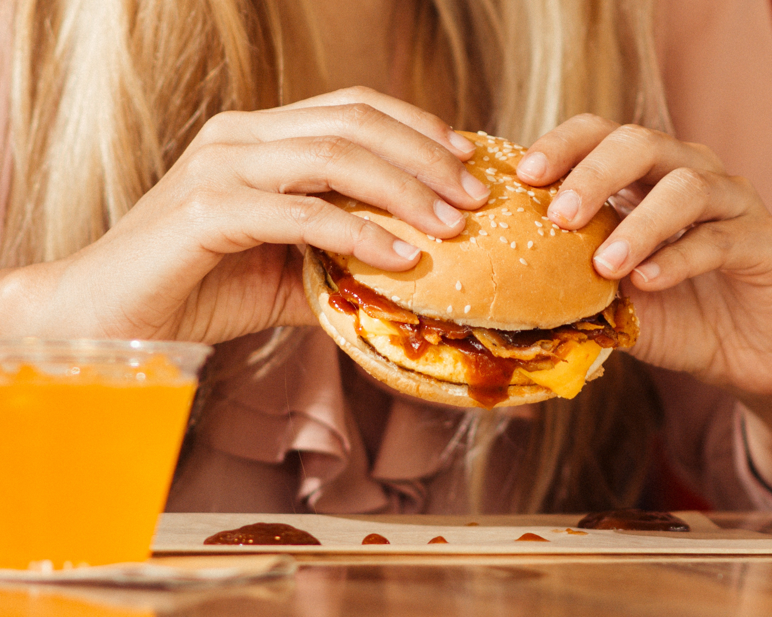 Woman with blonde hair holding burger