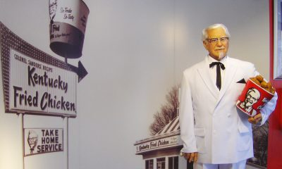 statue of KFC Col. Sanders in front of original KFC location poster