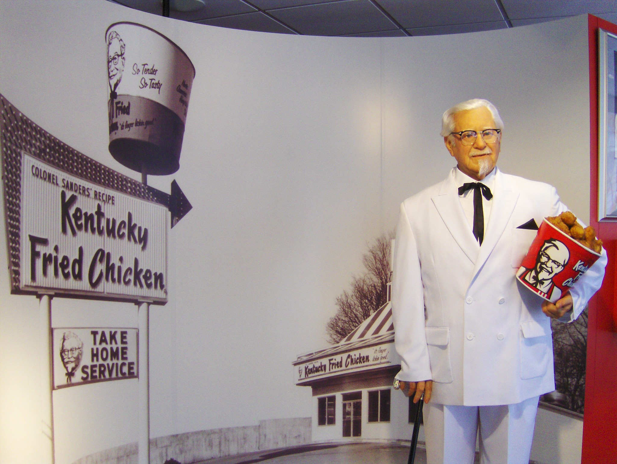 statue of KFC Col. Sanders in front of original KFC location poster