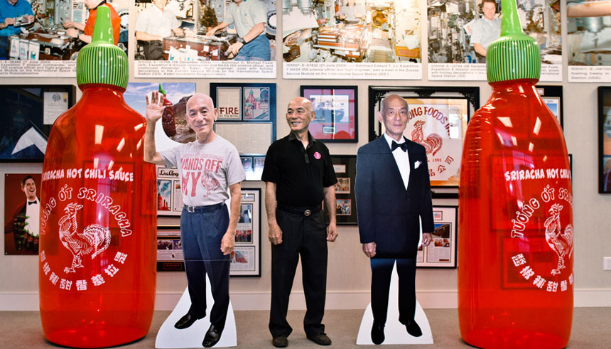 David-Tran-CEO-of-Huy-Fong-Foods-with-cutouts-of-himself-and-Sriracha-bottles-full1