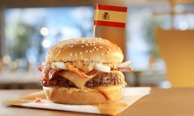 closeup of big burger with tiny Spanish flag on top