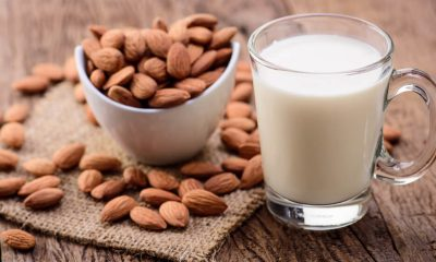 Almond milk jug sitting on table with bow of almonds