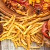 A pile of junk food (fries, pizza, sweets, etc.))