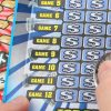 A person using a coin to use a scratch ticket